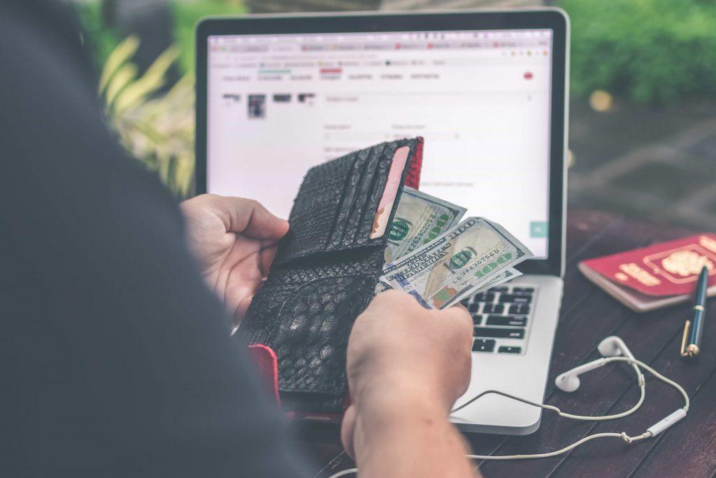 website kosten per maand, man die portemonnee voor zijn laptop houd